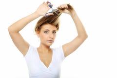 剪她的有剪刀的不快乐的妇女头发被隔绝 图库摄影