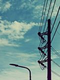 剪影、电岗位和灯岗位在蓝天 免版税库存图片