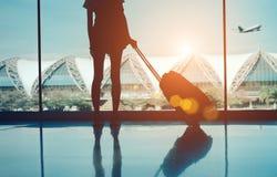 剪影与看,不用窗口的行李的妇女旅行 免版税库存照片