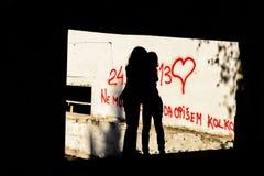 剪影两个小女孩拥抱 免版税库存图片