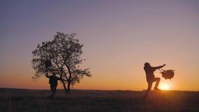 剪影两个远足者游人跑的跳跃滑稽和投掷挑运在日落 慢的行动 概念旅行和 股票视频
