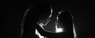 剪影两性感的妇女亲吻的通过举行在黑暗中 库存照片