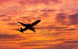 剪影乘客在日落的飞机飞行 免版税库存图片