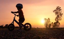 剪影亚洲孩子第一辆天戏剧平衡自行车 库存照片