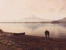剪影亚洲40s立场和作为pictur的夫妇旅客30s 库存图片