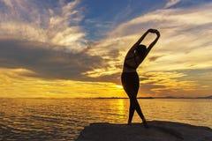 剪影健康妇女生活方式行使重要在海滩的岩石思考和实践的瑜伽在日落 图库摄影
