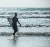 剪影冲浪者接近波浪,Fistral海滩,纽基,康沃尔郡 免版税库存图片