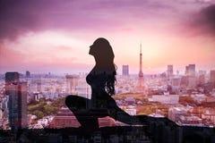 剪影反对东京市的瑜伽妇女两次曝光  免版税库存图片