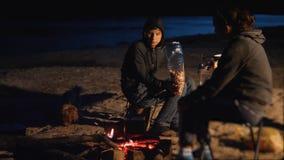 剪影哄骗青少年的孩子由吃玉米花的火坐在夜营火 远足冒险野营的旅行 股票录像