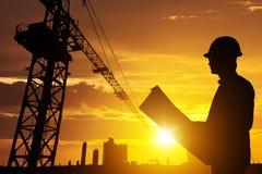 剪影商人工程师看图纸的在被弄脏的建造场所影片五谷进展的一个建筑工地和有力 免版税图库摄影
