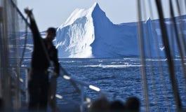 剪影在一座巨大的冰山前面的人 免版税库存照片