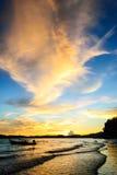 剪影在与橙色云彩的海岸后被设置的太阳 库存照片