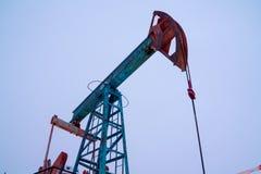 剪影在日落天空背景的油泵 石油工业设备 关闭工业看法在油 图库摄影