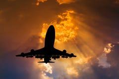 剪影在日落的飞机飞行 库存图片