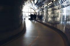剪影在步行者和骑自行车者的一个隧道尽头 库存照片