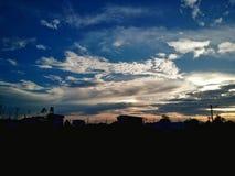剪影城市在strom前的多云天空背景 免版税库存图片