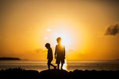 剪影太阳的两个常设男孩 免版税库存照片