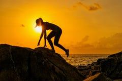 剪影女孩沿岩石跑由海在一个热带海岛上的黎明 库存图片