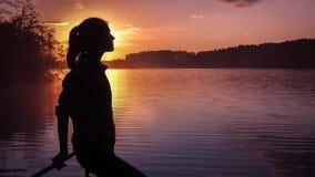 剪影女孩背景太阳 站立近的水的女孩户外 金子日落湖 考虑某事河du的少妇 库存照片