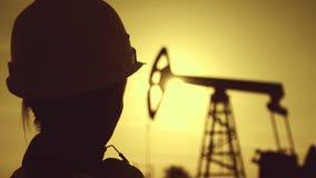 剪影妇女工程师佩带的白色盔甲和工作服在日落 工业,油和煤气概念 股票录像