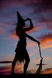剪影妇女巫婆的扫帚举行帽子 库存图片
