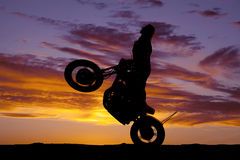 剪影妇女摩托车乘驾自行车前轮离地平衡特技 免版税图库摄影