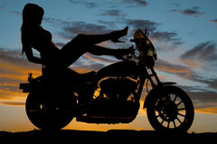 剪影妇女摩托车脚跟上升手下来 免版税库存照片