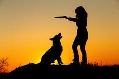 剪影妇女走与在领域的一条狗的在日落,使用与宠物的秋天夹克的一个女孩投掷木棍子  库存图片