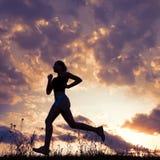 剪影妇女跑在与云彩的蓝天下 免版税库存照片