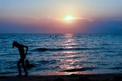 剪影妇女跑远离在海滩的孩子 免版税库存图片
