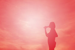 剪影妇女饮用水 免版税库存图片