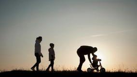 剪影家庭一起在日落 学会年轻的男孩骑自行车,父亲教他的儿子骑在的一辆自行车 股票录像
