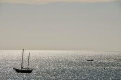 剪影小船在海洋 免版税库存照片