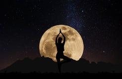 剪影少妇实践的瑜伽姿势在满月下的晚上与天空有很多星 免版税库存图片