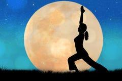 剪影少妇实践的瑜伽 免版税库存照片