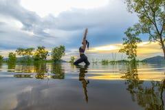 剪影少妇生活方式行使重要思考,并且实践反射在水洪水在水库, backgr的树 免版税库存图片