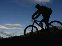 剪影山骑自行车的人 免版税库存图片