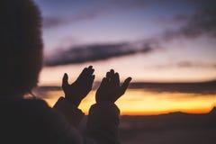 剪影年轻人的崇拜的手开放棕榈和祈祷对日出的,基督徒宗教概念背景神 免版税库存照片