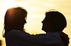 剪影拥抱母亲的女儿,笑,一起爱 免版税库存图片