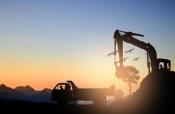 剪影挖掘机和卡车 库存图片