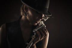 剪影有减速火箭的话筒的歌手妇女 免版税库存图片