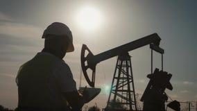 剪影有剪贴板的油脉动单元的工程师和证券监督原油的站点人 股票视频