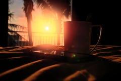 剪影杯子和智能手机在平衡太阳的温暖的橙色光芒 概念夏天晚上在热带 免版税库存图片