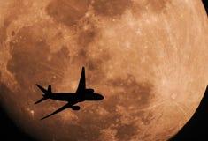 剪影横跨月亮的飞机飞行 免版税库存图片
