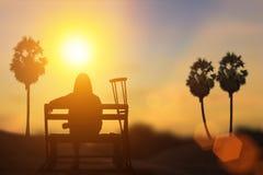 剪影残疾在轮椅或背景 免版税图库摄影
