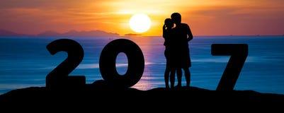 剪影浪漫夫妇拥抱亲吻反对夏天在日落暮色天空的海海滩,当庆祝新年好2017年时 图库摄影