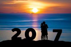 剪影浪漫夫妇拥抱亲吻反对日落暮色天空的夏天海,当庆祝新年好2017年时 库存照片