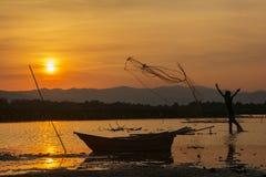 剪影渔人和日落 免版税库存照片