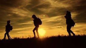 剪影父亲、母亲和儿童远足 婴孩坐他的父亲肩膀  远足迁徙的背包徒步旅行者 影视素材