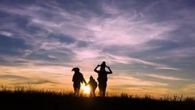 剪影父亲、母亲和儿童远足 婴孩坐他的父亲肩膀  远足迁徙的背包徒步旅行者 股票录像